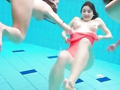 Three playful honeys swimming in the pool and taking off their bikini